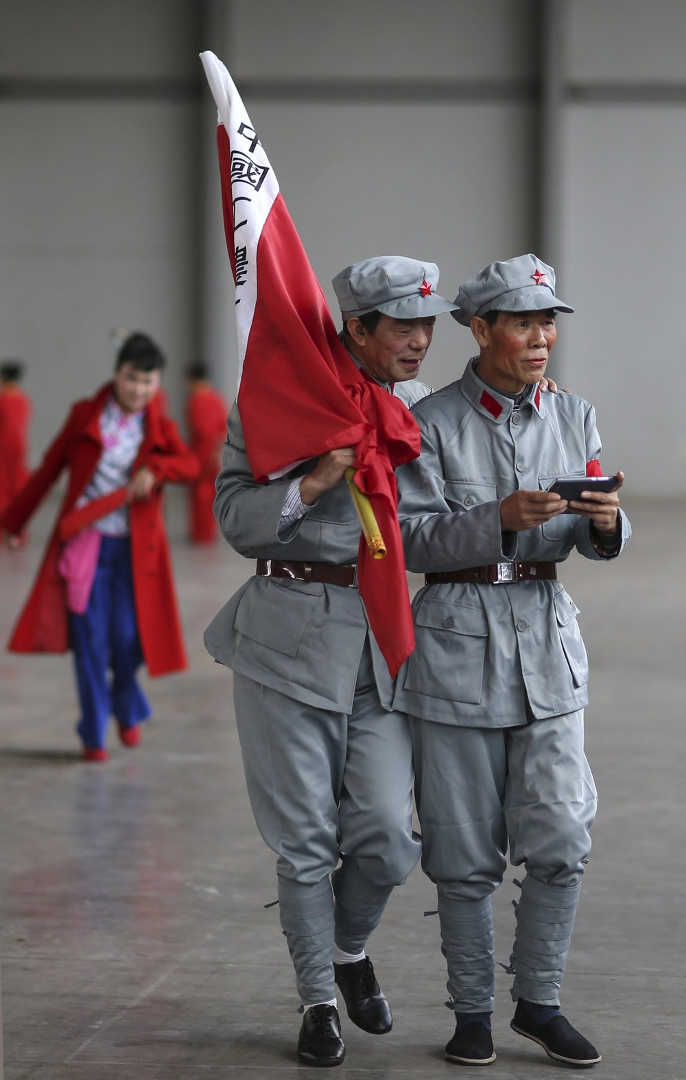 Participants dressed as Red Army soldiers look at a mobile phone as they wait backstage before their performance at a line dancing competition in Kunming